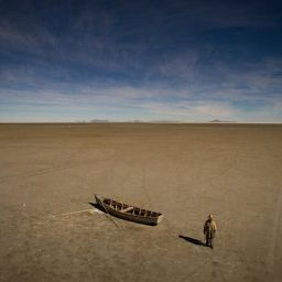 Felix Condori, 31, the mayor of Llapallapani and a former fisherman, next to a boat in the dry bed that was once Bolivia's second-largest lake. He now must travel to find construction jobs as a means to make money now that the lake that defined their culture and livelihood disappeared. May 2016.